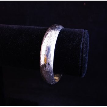 """Silver bangle with engraved decoration, push clasp and safety chain. Measures 2.25"""" diameter"""