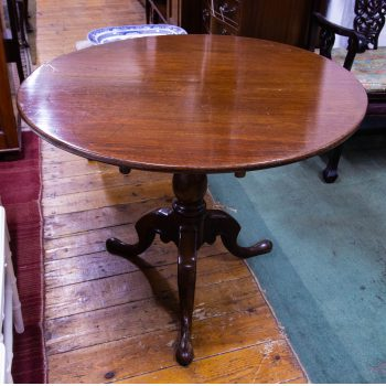 "Round mahogany tip up table on pod leg. Measures 36""W x 26""H"