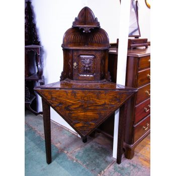 "Carved oak corner table with small cupboard door. Measures 31.5""L x 22.5""D (16.5""D leaf) x 53.5""H"